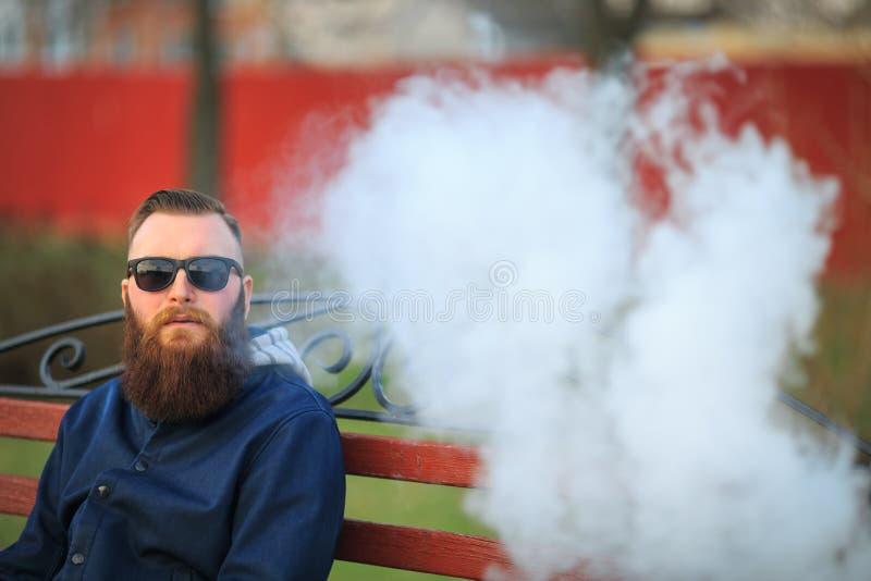 Vape 有大胡子和时兴的理发的年轻残酷人在太阳镜抽在红色长凳的一根电子香烟在t 免版税库存图片