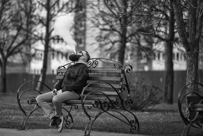 Vape 有大胡子和时兴的理发的年轻残酷人在太阳镜抽在红色长凳的一根电子香烟 免版税库存照片