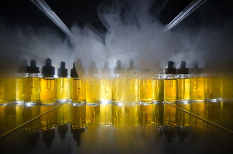 Vape begrepp Rökmoln och vapevätskeflaskor på mörk bakgrund stor ljus deltagarekapacitet för effekter royaltyfria bilder