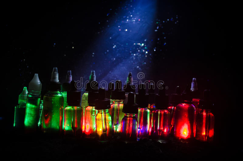 Vape begrepp Rökmoln och vapevätskeflaskor på mörk bakgrund stor ljus deltagarekapacitet för effekter royaltyfri fotografi