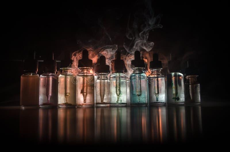 Vape begrepp Rökmoln och vapevätskeflaskor på mörk bakgrund stor ljus deltagarekapacitet för effekter Användbart som bakgrunds- e arkivbild