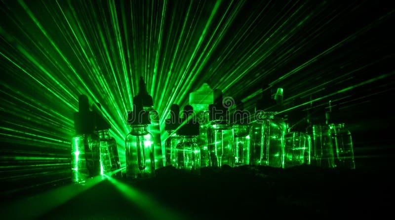 Vape begrepp Rökmoln och vapevätskeflaskor på mörk bakgrund stor ljus deltagarekapacitet för effekter Användbart som bakgrunds- e royaltyfri fotografi