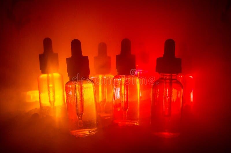 Vape begrepp Rökmoln och vapevätskeflaskor på mörk bakgrund stor ljus deltagarekapacitet för effekter Användbart som bakgrunds- e arkivbilder