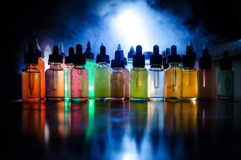 Vape begrepp Rökmoln och vapevätskeflaskor på mörk bakgrund stor ljus deltagarekapacitet för effekter Användbart som bakgrunds- e royaltyfri foto