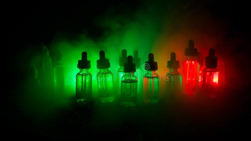 Vape concept. Smoke clouds and vape liquid bottles on dark background. Light effects. Useful as background or electronic cigarette royalty free stock images