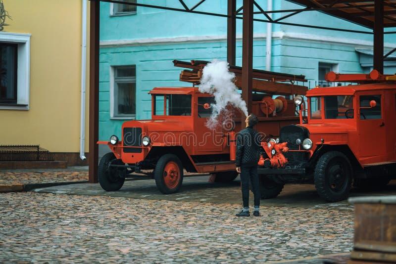 Vape Ein junger hübscher Kerl ist stehendes nahes altes Löschfahrzeug und lässt weg vom Dampf von einer elektronischen Zigarette lizenzfreies stockbild
