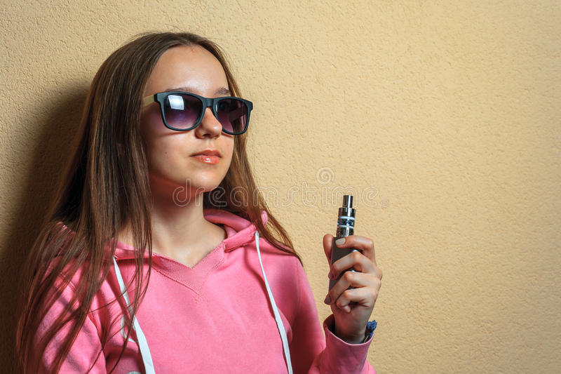 Vape girl. Portrait of young cute woman in pink hoodie and sunglasses holding an electronic cigarette in her hand opposite sienna royalty free stock images