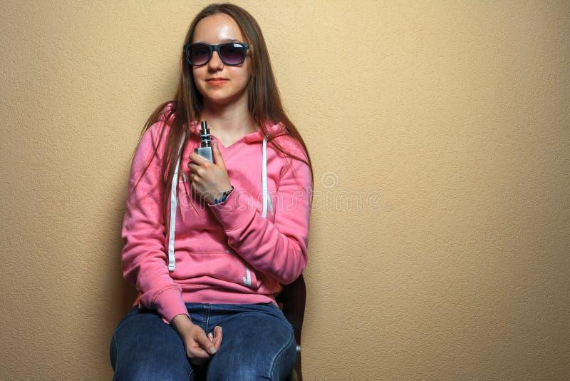 Vape-Mädchen Porträt der jungen netten Frau im rosa Hoodie und in der Sonnenbrille, die eine elektronische Zigarette in ihrer Han stockfotografie