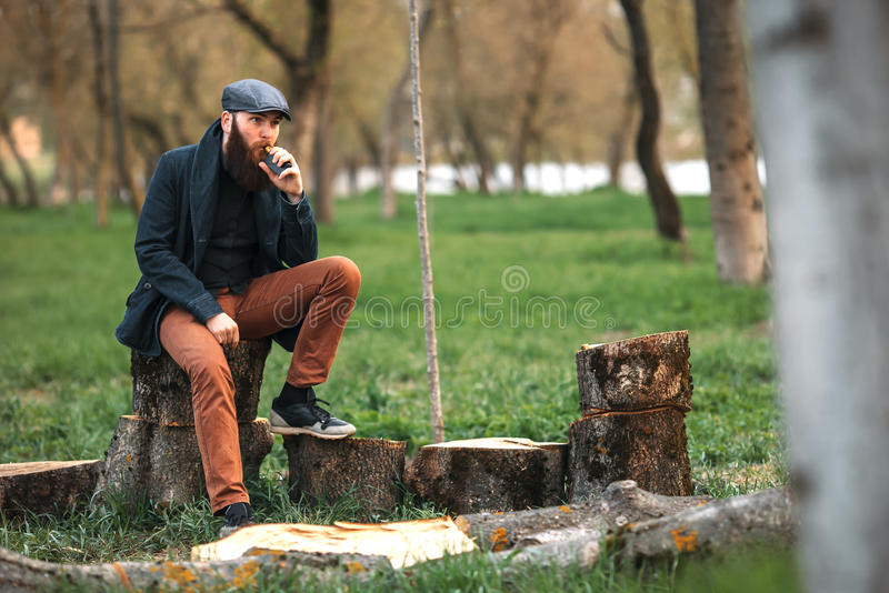 Vape man Fotoet av brutal skäggig ung man som en har, vilar, når kotlettvedträ och det har vaping en elektronisk cigarett i byn arkivfoton