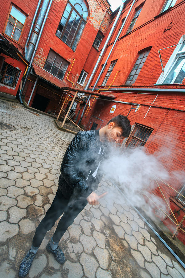 Vape man. A handsome young white guy in glasses blows steam from an electronic cigarette in a vintage old red yard. royalty free stock photos