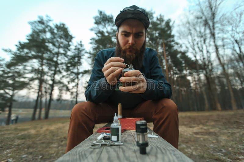 Vape O homem novo com grande barba em um tampão armazena o algodão em um cigarro eletrônico fotografia de stock royalty free