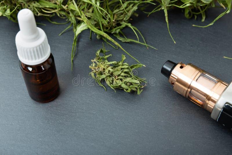 Vape pen and medical marijuana hemp bud. CBD and THC oil vaping products. In a natural light stock photo