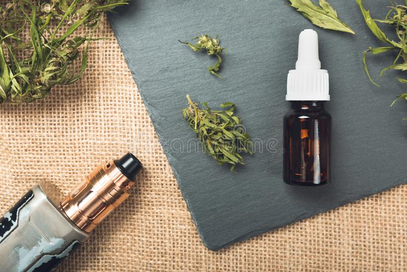 Vape pen and medical marijuana hemp bud. CBD and THC oil vaping products. In a natural light stock image