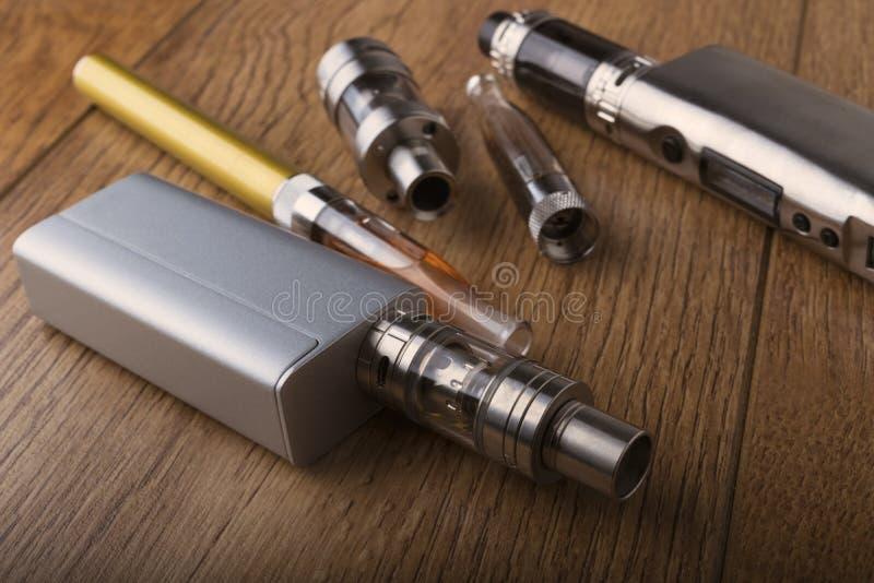 Vape penna och vaping apparater, mods, sprejflaskor, e-cig, e-cigarett royaltyfri foto