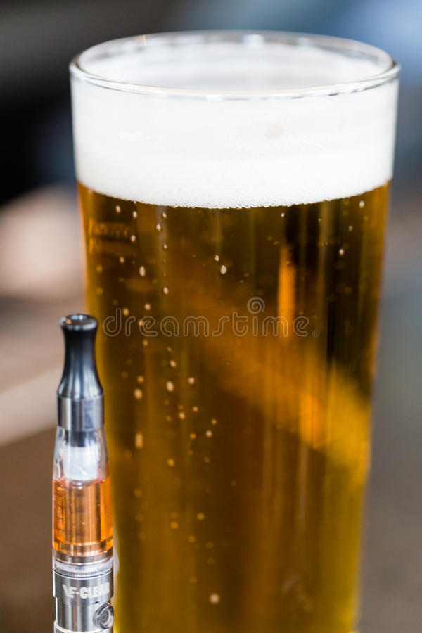 Vape pipe beside beer royalty free stock image