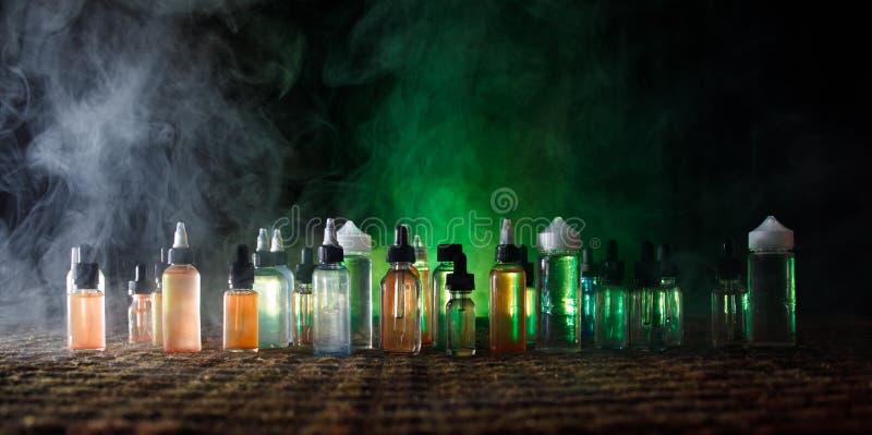 Vape pojęcie Dymne chmury i vape ciekłe butelki na ciemnym tle skutków wielki światła przyjęcia występ Pożytecznie jako tła lub v obraz stock