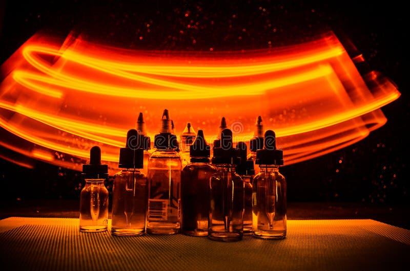 Vape pojęcie Dymne chmury i vape ciekłe butelki na ciemnym tle skutków wielki światła przyjęcia występ obraz royalty free