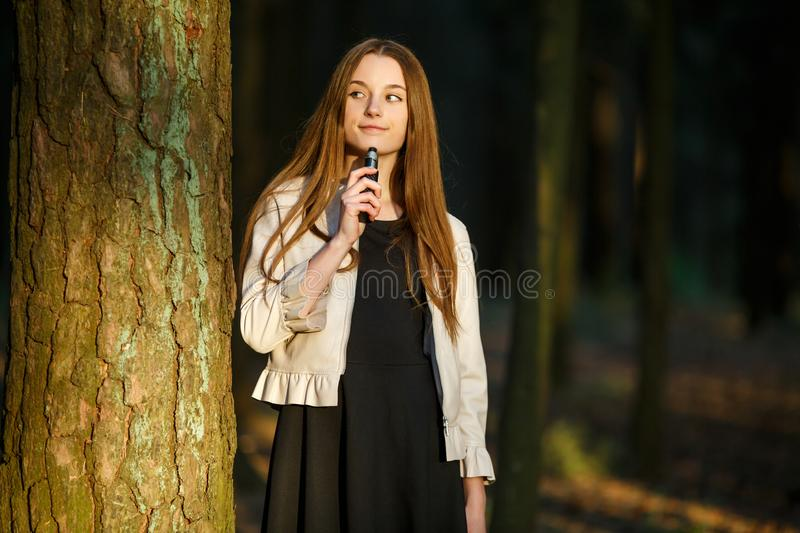 Vape teenager. Young cute girl in casual clothes smokes an electronic cigarette outdoors in the forest at sunset in summer. royalty free stock photo