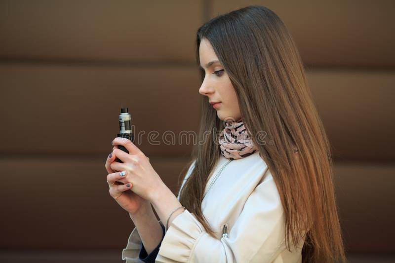 Vape teenager. Young white girl in casual clothing smoking an electronic cigarette opposite modern brown background on the street. royalty free stock photos