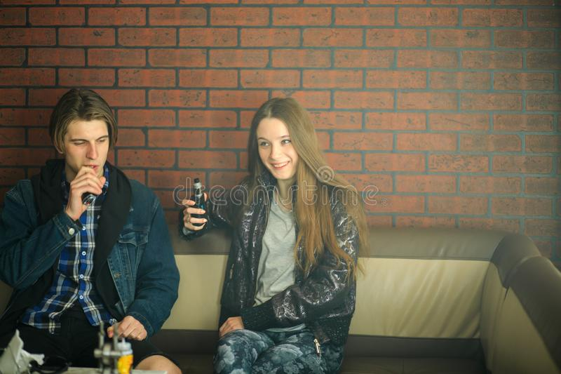 Vape teenagers. Young cute girl and young handsome guy smoke an electronic cigarettes in the vape bar. Bad habit stock images
