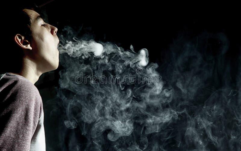 Vape trick rings in performance of vaper on dark background royalty free stock photo