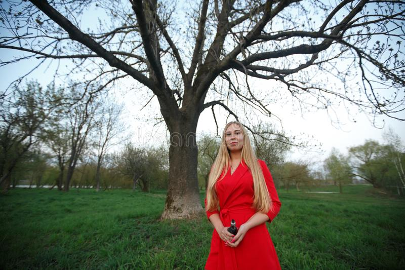Vape woman. Young beautiful blonde girl in red dress smokes an electronic cigarette opposite big tree in the park in the evening. royalty free stock photos