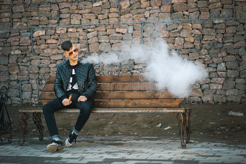 Vape. A young handsome guy sits on the bench and blows steam from an electronic cigarette. stock photos