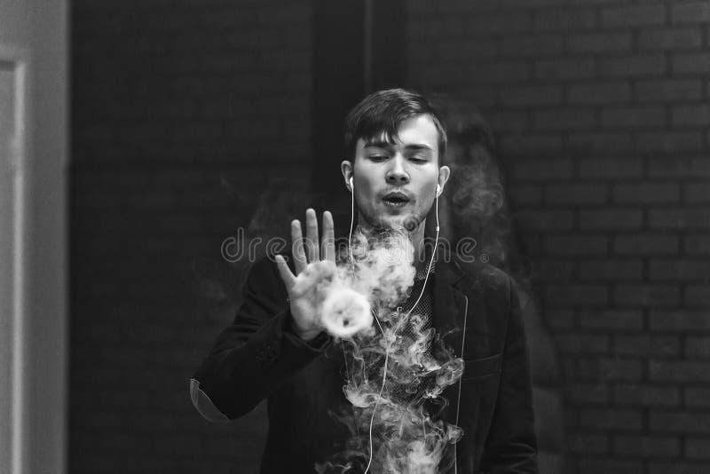 Vapemens De jonge knappe witte kerel liet ringen uit stoom van elektronische sigaret De Zwart-witte foto van Peking, China royalty-vrije stock foto's