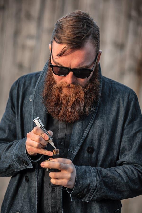 Vapemens Openluchtportret van een jonge brutale witte kerel met grote baard die elektronische sigaret tegenover de oude houten om stock foto's