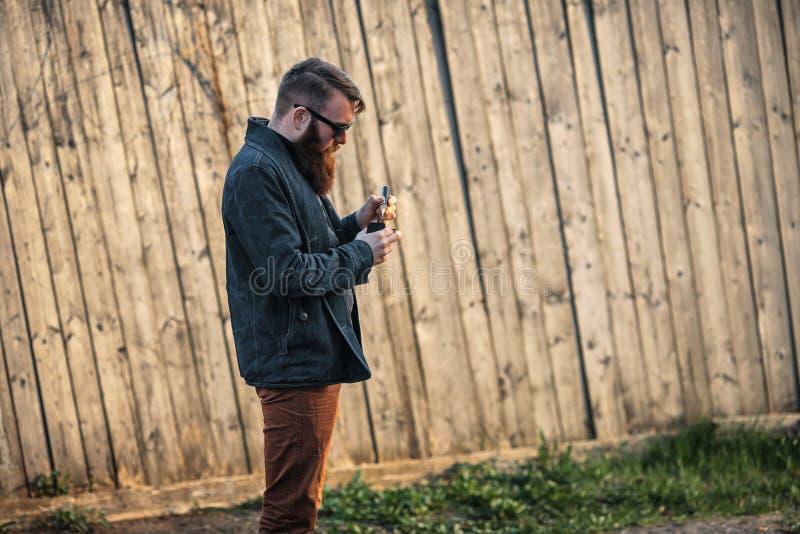Vapemens Openluchtportret van een jonge brutale witte kerel met grote baard die elektronische sigaret tegenover de oude houten om stock afbeelding