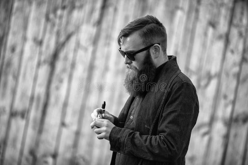 Vapemens Openluchtportret van een jonge brutale witte kerel met grote baard die elektronische sigaret tegenover de oude houten om stock foto