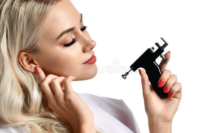 Vapen för piercing för öra för håll för kvinnakosmetologcosmetologist som ser hörnet som isoleras på vit royaltyfri fotografi