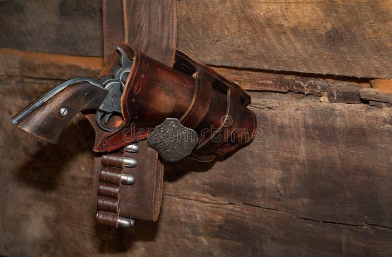 Vapen i pistolhölster mot träbakgrund arkivbild
