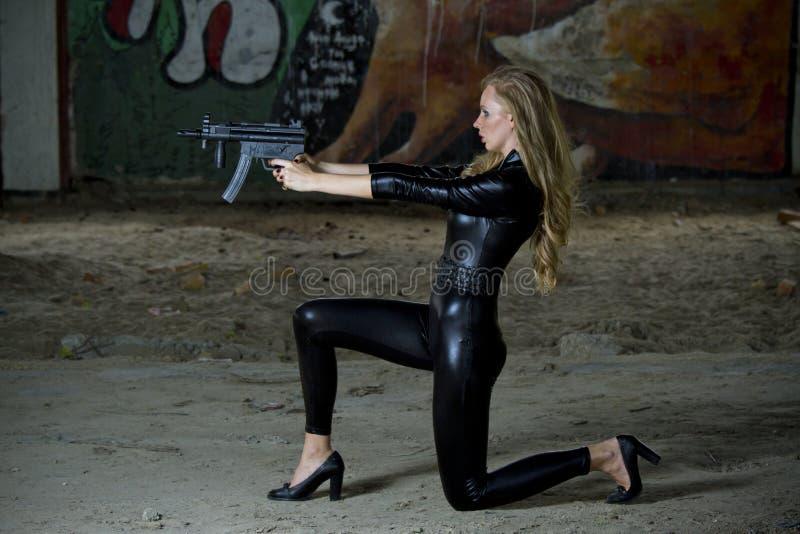 Vapenkvinna i lädercatsuit arkivbild