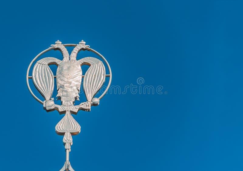 Vapensk?lden av Ryssland, f?rsilvrar denh?vdade ?rnen mot bakgrunden av bl? himmel F?rsilvra det ryska heraldiska symbolet, bakgr royaltyfri bild