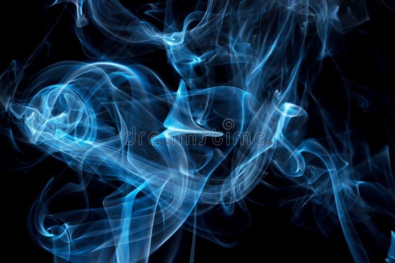 Vapeur bleue sur le fond noir images stock