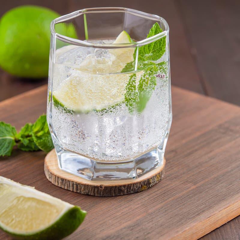 Vapeur de cocktails Mojito Monnaie, citron vert, verre et ciseaux photo stock