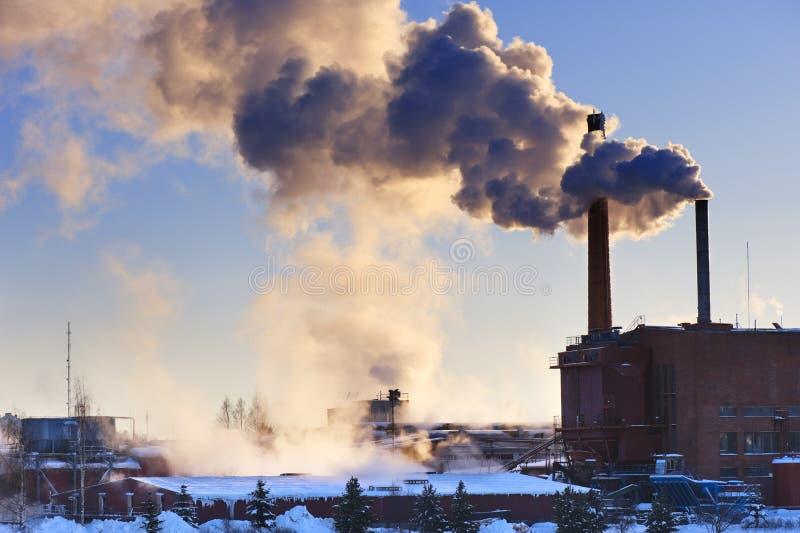 Vapeurs d'usine et d'échappement soufflées dans un ciel photographie stock libre de droits