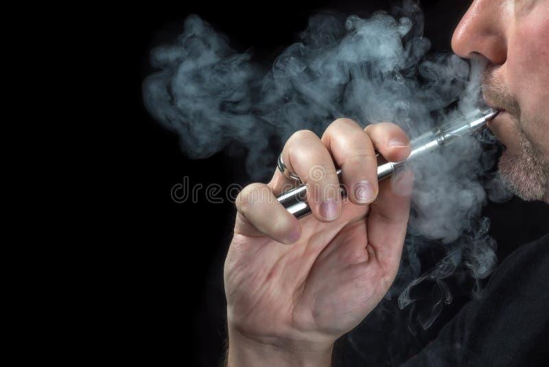 vaping一根电子香烟的一个人的特写镜头 图库摄影