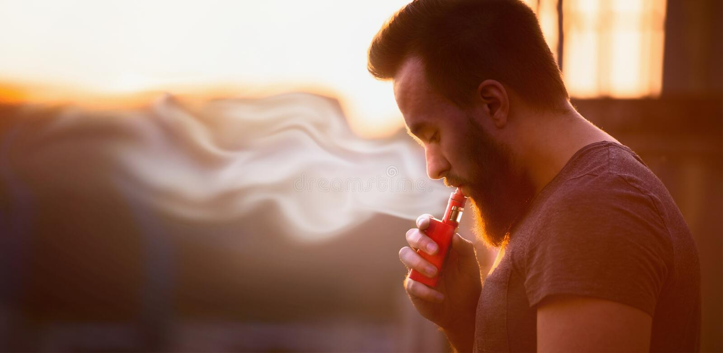 Vaping, junger Mann mit einem Bart, produziert Dampfsonnenuntergang-Himmelhintergrund, Platz für Text lizenzfreies stockfoto