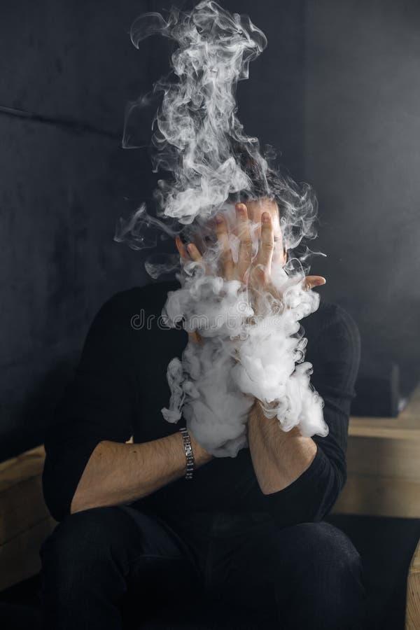 Vaping mężczyzna trzyma mod Chmura opary Czarny tło zdjęcia stock