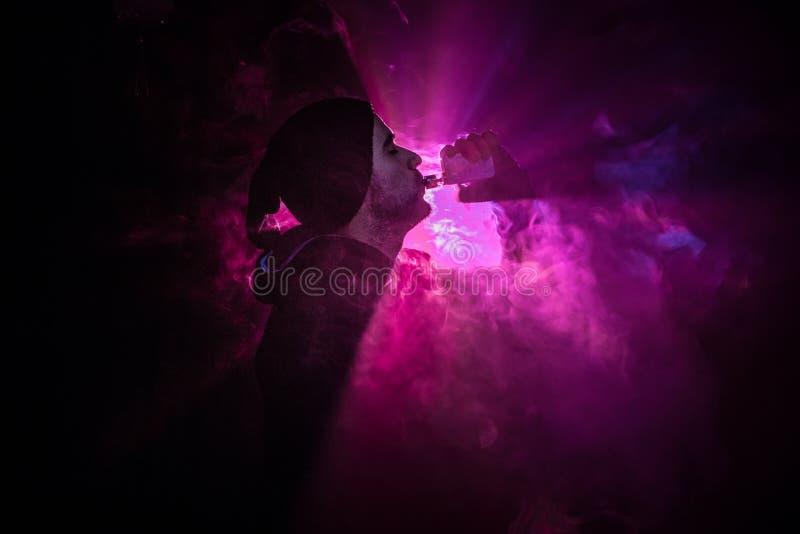Vaping mężczyzna trzyma mod Chmura opary Czarny tło Vaping elektroniczny papieros z mnóstwo dymem Vape pojęcie obrazy stock