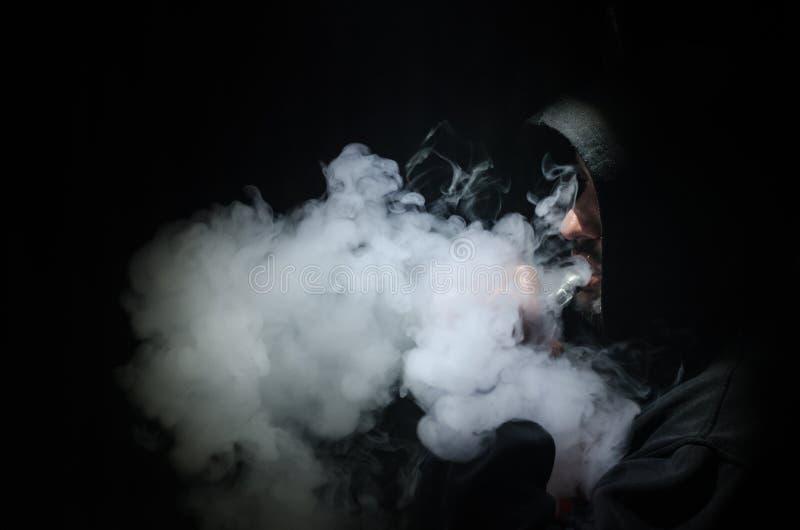 Vaping mężczyzna trzyma mod Chmura opary Czarny tło Vaping elektroniczny papieros z mnóstwo dymem zdjęcia royalty free
