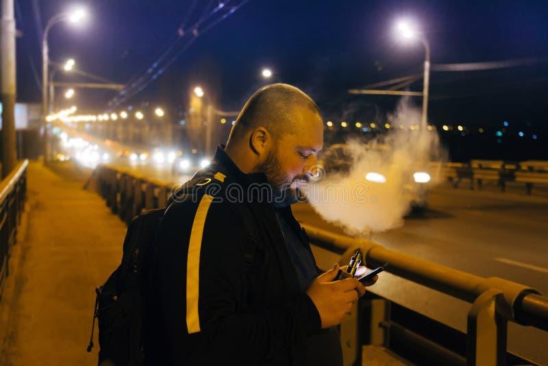 Vaping por el hombre gordo del cigarrillo electrónico que usa el Smart-teléfono en el puente en la ciudad de la noche foto de archivo