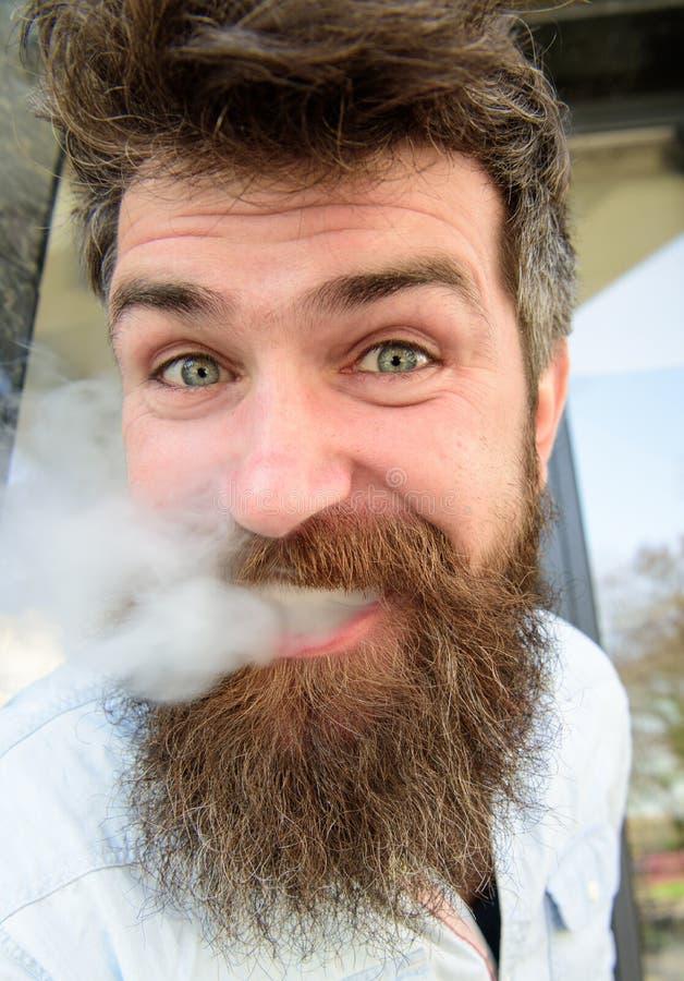 Vapingsconcept Hipster met slonzig haar en grijs op ontspannen vrolijk gezicht met witte rook die uit mond vliegen Mens stock fotografie
