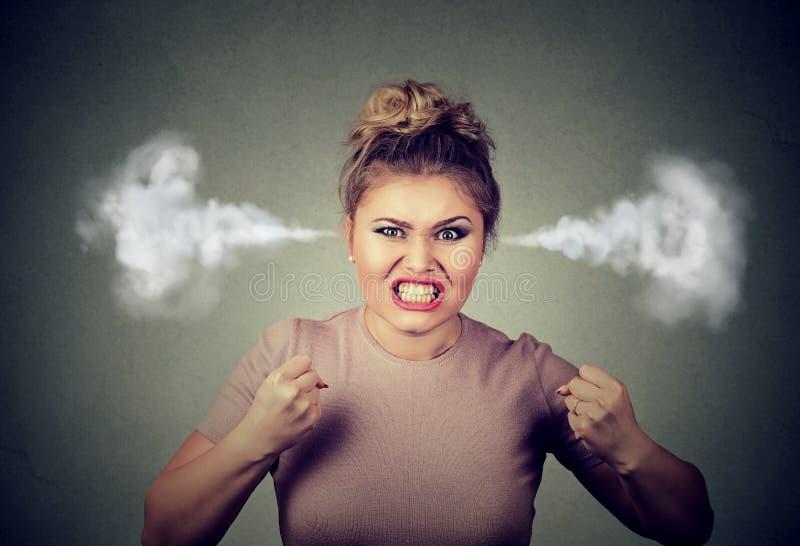 Vapor de sopro da mulher irritada que sai das orelhas aproximadamente para ter a divisão nervosa que grita fotografia de stock