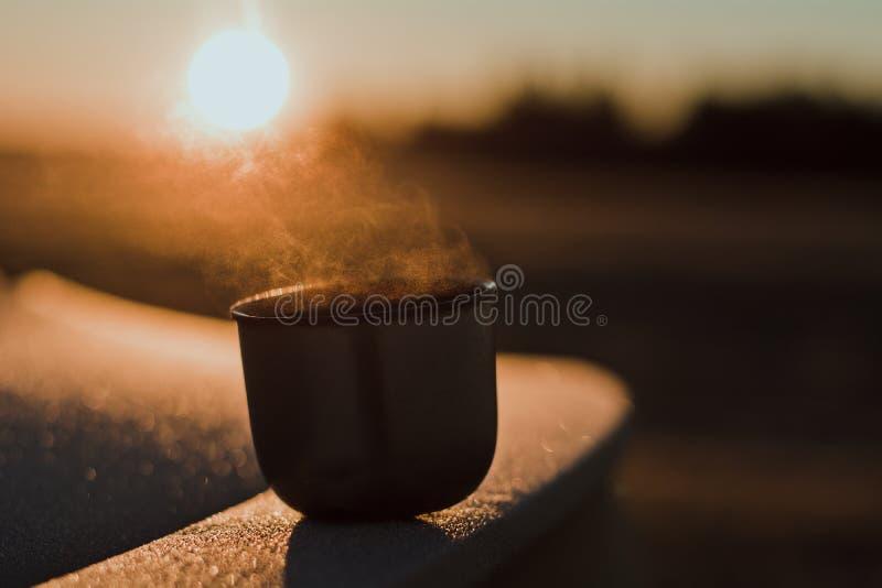 Vapor de uma caneca quente do chá de uma garrafa térmica, que seja iluminada pelo sol da manhã do inverno na luz calma imagens de stock