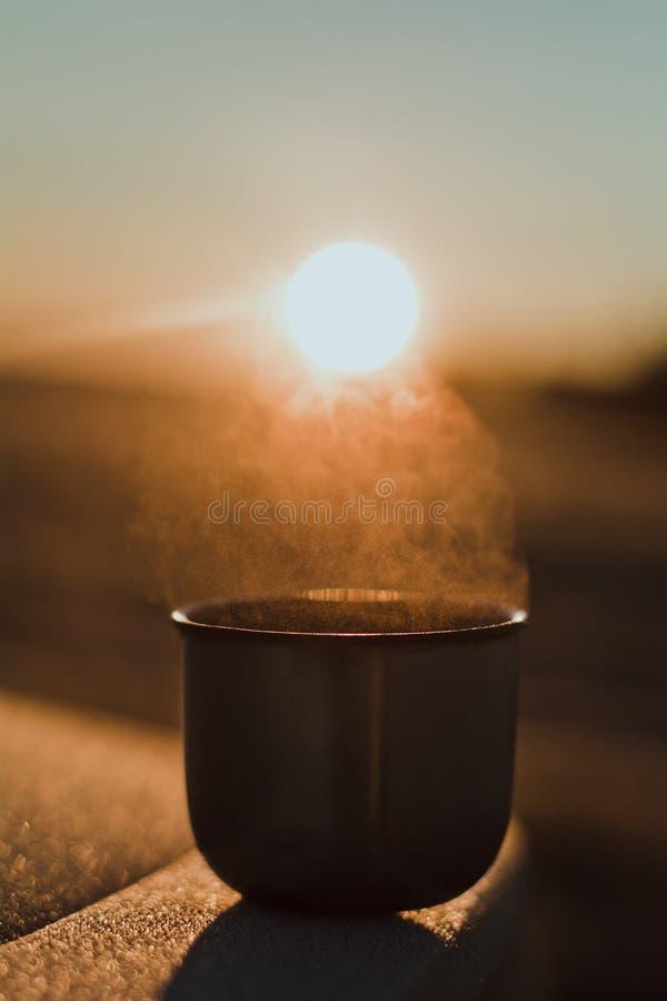 Vapor de uma caneca quente do chá de uma garrafa térmica, que seja iluminada pelo sol da manhã do inverno na luz calma imagem de stock royalty free