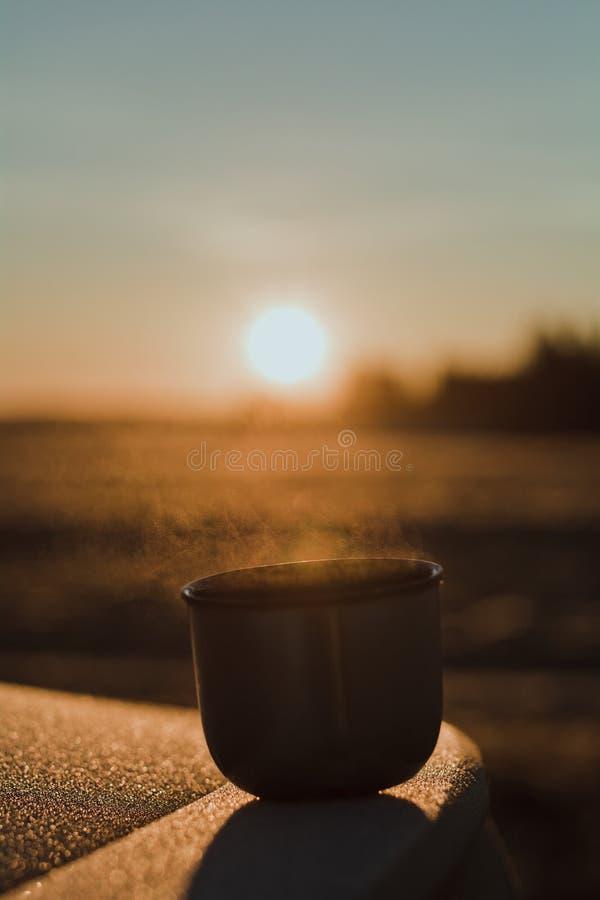 Vapor de uma caneca quente do chá de uma garrafa térmica, que seja iluminada pelo sol da manhã do inverno na luz calma foto de stock royalty free