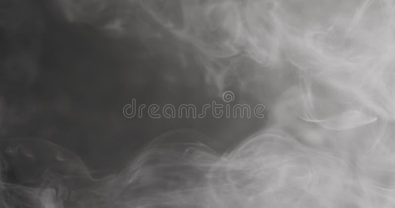 Vapor do close up do movimento lento que flutua no ar no fundo preto imagem de stock